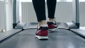 Trampkvarn manfot i sportskor på simulatorn i idrottshall lager videofilmer