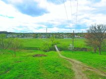 Trampled path along the sides of which grows green grass, trees. Blue sky. A village with houses. Stock Photography