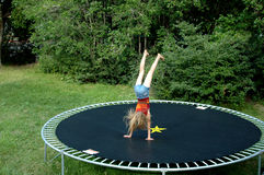 Tramploine fun. Girl on family backyard trampoline Stock Photos