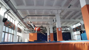 Trampoline girl doing simply workout,. Handsome trampoline girl doing simply workout inside gymnastic hall stock video footage