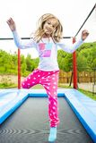 Trampoline Girl Jump. Happy girl jumping high on a trampoline on a sunny day outdoors stock photos