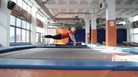 Trampoline girl jumping high in the air,. Pretty trampoline girl is jumping high in the air in gymnastic hall stock video