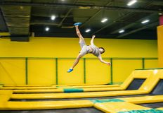 Trampoline jumper performs acrobatic exercises on the trampoline. Trampoline jumper performs complex acrobatic exercises and somersault on the trampoline royalty free stock photo