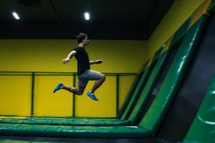 Trampoline jumper performs acrobatic exercises on the trampoline. Trampoline jumper performs complex acrobatic exercises and somersault on the trampoline royalty free stock images