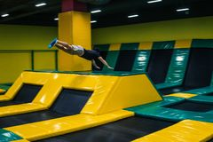 Trampoline jumper performs acrobatic exercises on the trampoline. Trampoline jumper performs complex acrobatic exercises and somersault on the trampoline royalty free stock image