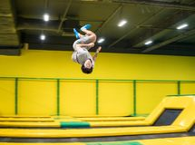 Trampoline jumper performs acrobatic exercises on the trampoline. Trampoline jumper performs complex acrobatic exercises and somersault on the trampoline stock image