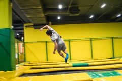 Trampoline jumper performs acrobatic exercises on the trampoline. Trampoline jumper performs complex acrobatic exercises and somersault on the trampoline stock photos