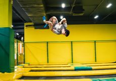 Trampoline jumper performs acrobatic exercises on the trampoline. Trampoline jumper performs complex acrobatic exercises and somersault on the trampoline stock photo