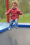 Trampoline jumping. SMall biracial boy toddler busy jumping on trampoline looking in the camera Royalty Free Stock Photo