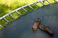 Trampoline mit Flipflops Stockfoto
