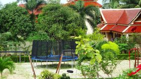 Trampoline with net and playground around at yard of homestead in tropical jungle. 3840x2160 stock video