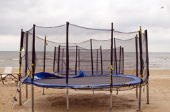 Trampolines on beach sea sand. Active recreation. Trampolines with protective net wall on beach coast sand. Active recreation near sea Stock Image