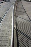 Tramrail, bestrating, traliewerk, metaalbeschermingsomheining en schaduwen royalty-vrije stock afbeeldingen