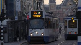 Trams cross paths on Damrak in Central Amsterdam. Taken at dawn the trams have their lights on. Shot in 4K stock video