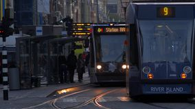Trams cross paths on Damrak in Central Amsterdam. Taken at dawn the trams have their lights on. Shot in 4K stock footage