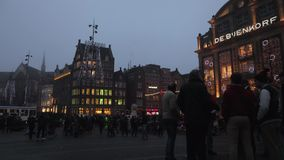 Trams drives by the City Hall on Dam Square in rush hour at foggy twilight. Time Lapse. AMSTERDAM, NETHERLANDS - JANUARY 03, 2017: Trams drives by the City Hall stock footage