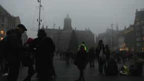 Trams drives by the City Hall on Dam Square in rush hour at foggy twilight. Time Lapse. stock footage