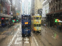 Trams in Hong Kong through wet window. Blurred city background Stock Image