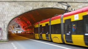 Trams and other vehicles hurrying, moving out from under bridge on wide motorway. Stock footage stock footage