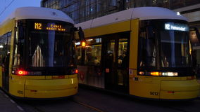 Night time video of trams and passengers at Alexanderplatz Station, Berlin, Germany. TRAMS AND PASSENGERS OUTSIDE ALEXANDERPLATZ TRAM AND TRAIN STATION, BERLIN stock video