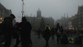 Tramwaje jadą urzędem miasta na tama kwadracie w godzinie szczytu przy mgłowym zmierzchem Czasu upływ zbiory