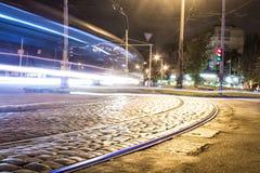 Tramwaju ślad na bruku przy nocą i poruszający samochód z plamą zaświecamy Zdjęcie Stock