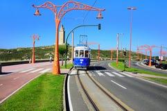 Tramway line on the city embankment. LA CORUNA, SPAIN - JUNE 20, 2010: Retro tramway carriage on the city embankment and Hercules tower, La Coruna, Spain, June Royalty Free Stock Photos