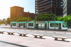Tramway moderne sur sa station avec des bâtiments derrière elle Photos libres de droits