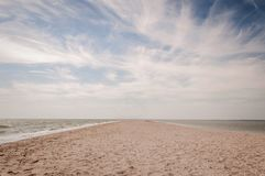 Trança da areia que entra no mar de Azov e no céu nebuloso foto de stock royalty free
