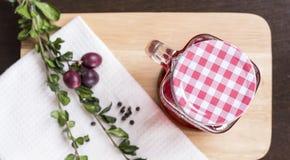 Tranbärfruktsaft i exponeringsglas på den lekmanna- skärbrädalägenheten Arkivbilder