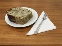 Tranche épaisse de gâteau avec l'écrimage de chocolat d'un plat blanc sur une table en bois Photographie stock libre de droits