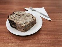 Tranche épaisse de gâteau avec l'écrimage de chocolat d'un plat blanc sur une table en bois Photo libre de droits