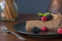Tranche appétissante de gâteau au fromage de chocolat avec des baies image libre de droits