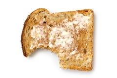 Tranche beurrée de pain grillé de blé entier d'isolement sur le blanc d'en haut photo libre de droits