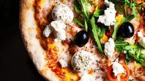 Tranche chaude de pizza avec le salami, les olives et le fromage de chèvre sur un rustique Photos libres de droits