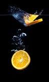 Tranche d'orange dans l'eau avec des bulles Image libre de droits