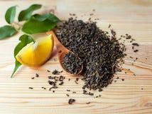 Tranche de citron et cuillère des feuilles de thé vertes sèches sur le backgr en bois Image libre de droits