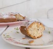 Tranche de ` de Ciambellone de ` de gâteau avec des miettes du plat en céramique peint avec des motifs floraux Images libres de droits