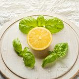Tranche de fruit de citron et groupe de feuilles de basilic Image stock