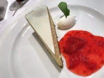 Tranche de gâteau au fromage avec le coulis de framboise du côté Photos libres de droits