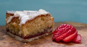 Tranche de gâteau au goût âpre de bakewell sur le plateau en bois olive, montrant des couches d'éponge et de confiture, avec la f Photographie stock libre de droits