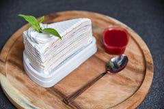 Tranche de gâteau de crêpe avec de la sauce à fraise sur la cuillère en bois de plat et le morceau foncé de fond d'arcs-en-ciel d photos stock