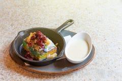 Tranche de gâteau d'arc-en-ciel avec avec de la sauce à vanille dans un café Gâteau dans le plat de fonte image stock