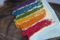 Tranche de gâteau d'arc-en-ciel avec le givrage bleu sur la surface en bois foncée Image stock
