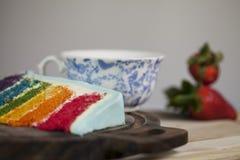 Tranche de gâteau d'arc-en-ciel avec le givrage bleu sur la surface en bois foncée Photos stock