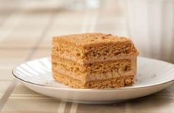 Tranche de gâteau de miel posé Image stock