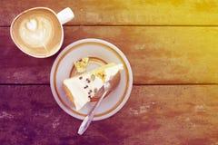 Tranche de gâteau fait maison de potiron avec la tasse de latte sur la table en bois dans la lumière chaude du soleil photographie stock