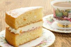 Tranche de gâteau mousseline de Victoria avec une boisson chaude Photos stock
