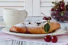 Tranche de la tarte aux cerises faite maison, tasse de café, cuvette avec des cerises Photo stock