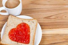 Tranche de pain délicieuse avec la forme de coeur de confiture de fraise Photographie stock libre de droits